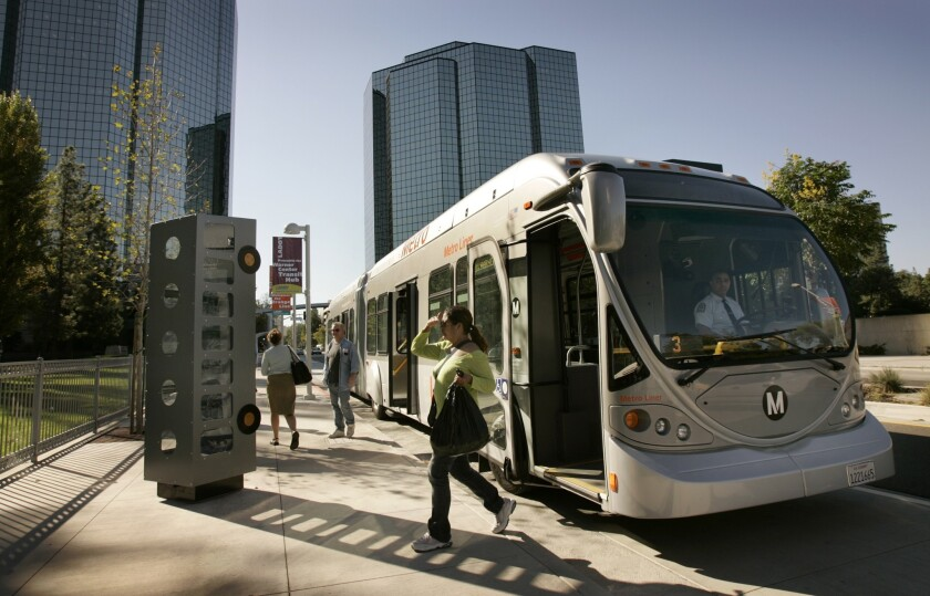Morning commuters get off an Orange Line bus at the Warner Center Station in the west end of the San Fernando Valley.