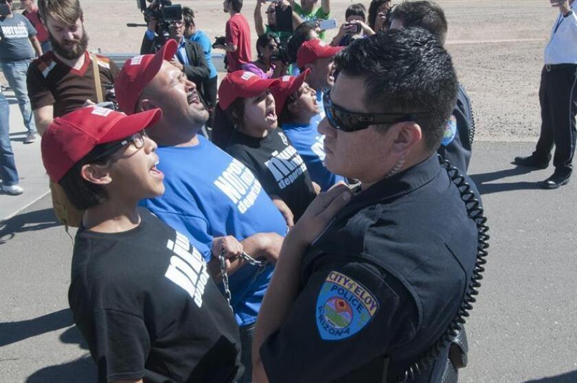 Unos policías intentan contener a unos participantes en un acto de desobediencia civil, el lunes 14 de cotubre 2013, en las afueras del Centro de Detenciones de Inmigración de Eloy en Arizona. EFE/Archivo