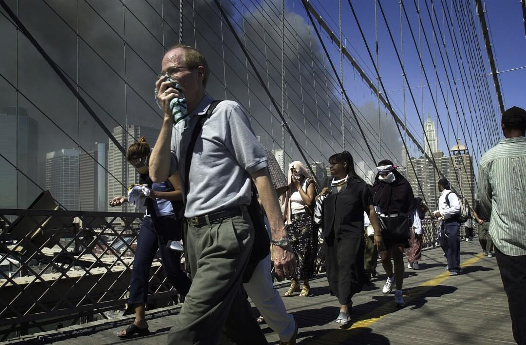 مردم از پل بروکلین عبور می کنند و دود در پس زمینه بلند می شود
