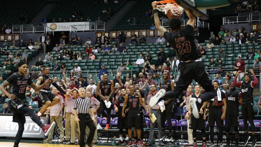The New Mexico State Aggies bench erupts as Zach Lofton dunks the ball in the final seconds of the semi-final game of the Diamond Head Classic against the Miami Hurricanes.