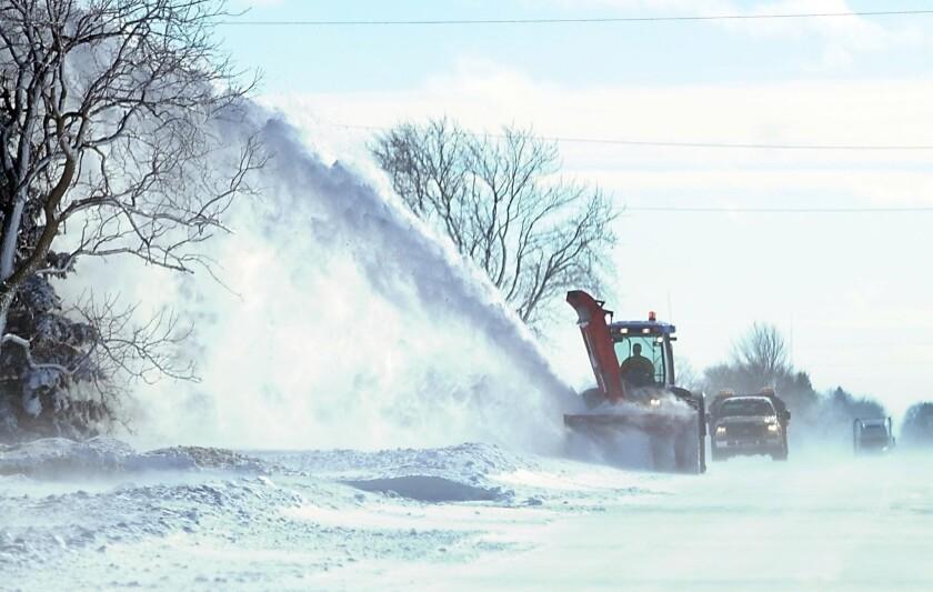 A large snowblower clears drifts from a highway near Mapleton, Minn., last week.