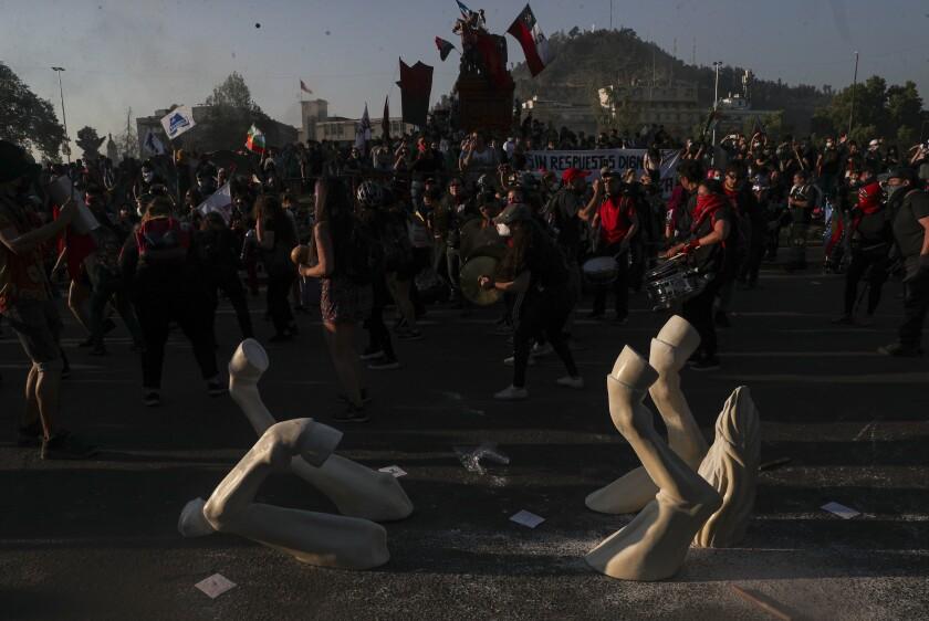 Manifestantes contra el gobierno protestan junto a la instalación de un caballo patas arriba del artista Maireni