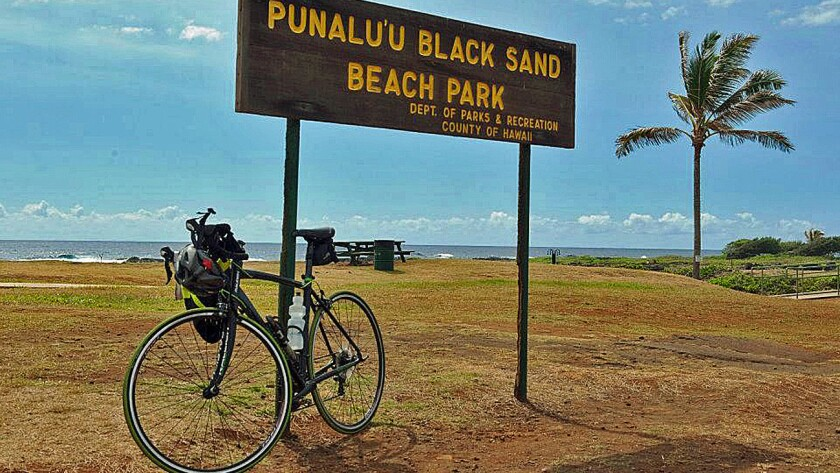 A black sand beach is among the stops for cyclists during tours of the Big Island of Hawaii.