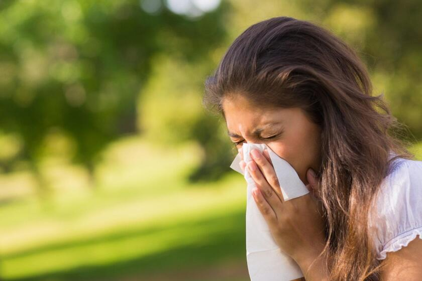 A woman blows her nose at the park