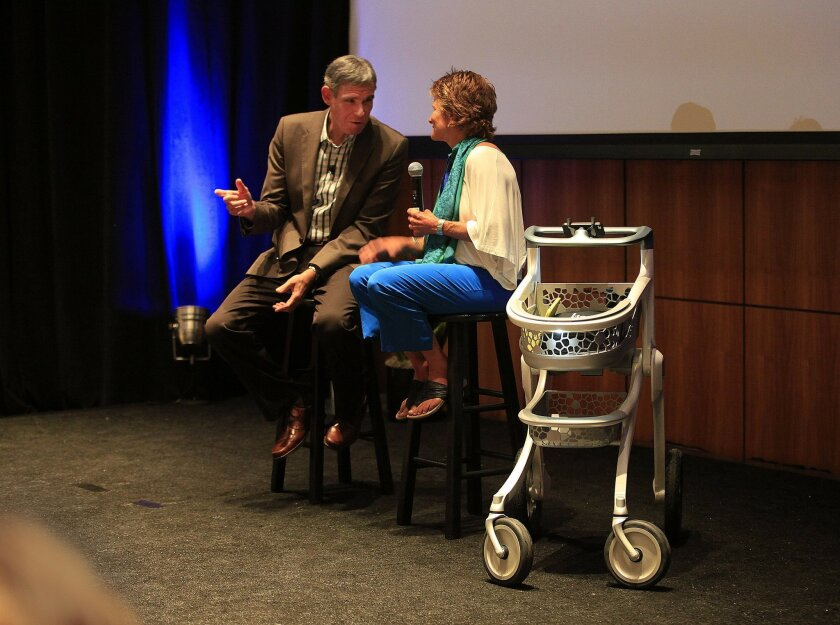 Dr. Eric Topol talks with Kim Goodsell on the stage at the Future of Genomic Medicine Conference, alongside her Pedestrian Assistive Technology created by Carlsbad-based DDStudio.