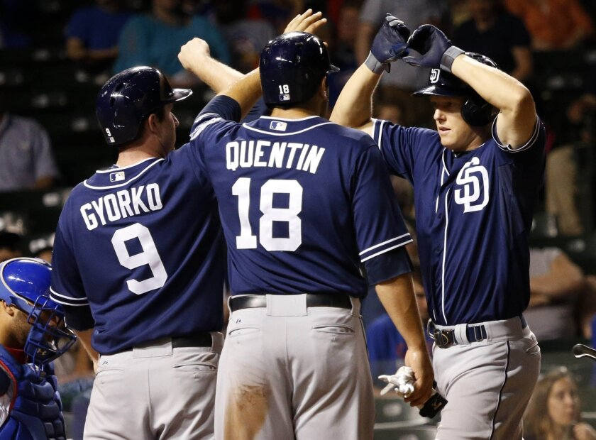 The Padres' Nick Hundley is greeted by Jedd Gyorko and Carlos Quentin after hitting a three-run homer in the eighth inning against the Cubs on Tuesday.