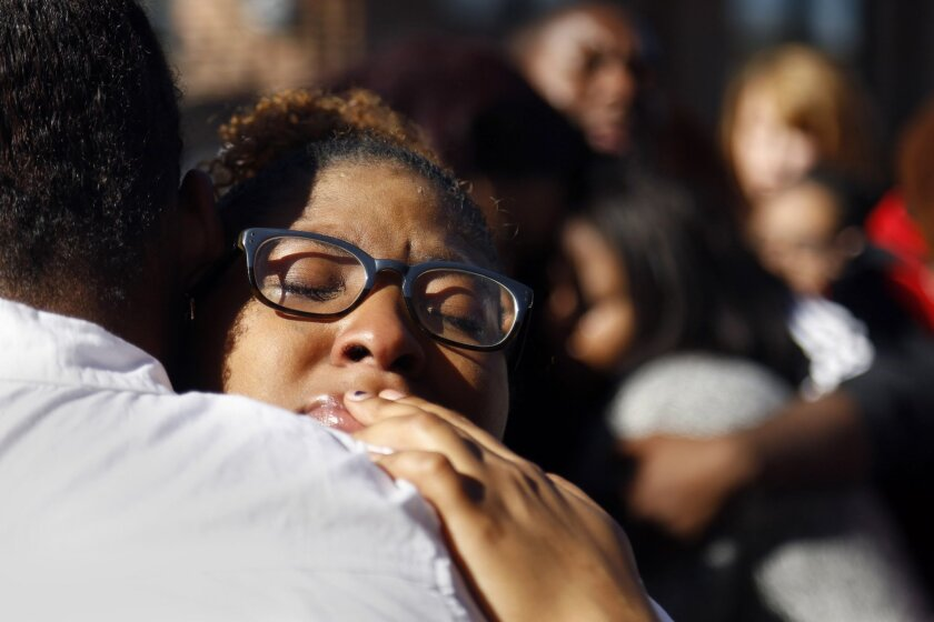 In this Saturday, Nov. 7, 2015, photo, a member of Concerned Student 1950 hugs a fellow protestor after the group prayed together in front of the Reynolds Alumni Center on the University of Missouri campus in Columbia, Mo. Some campus groups have been protesting the way university president Tim Wol