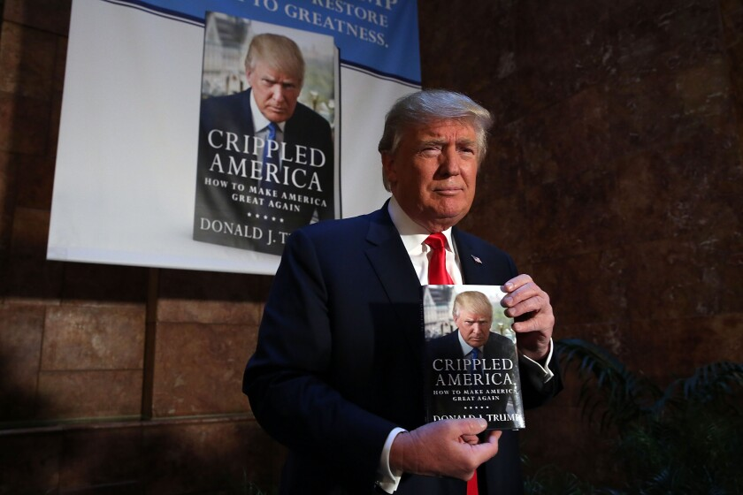 "President Donald Trump holds a copy of his book ""Crippled America: How to Make America Great Again"" in 2015."