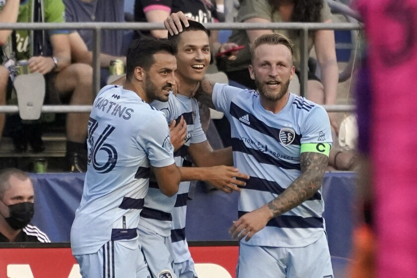 Sporting Kansas City forward Daniel Salloi, center, celebrates with defender Luis Martins (36) and Johnny Russell, right, after Salloi scored a goal against the Seattle Sounders during the first half of an MLS soccer match, Sunday, July 25, 2021, in Seattle. (AP Photo/Ted S. Warren)