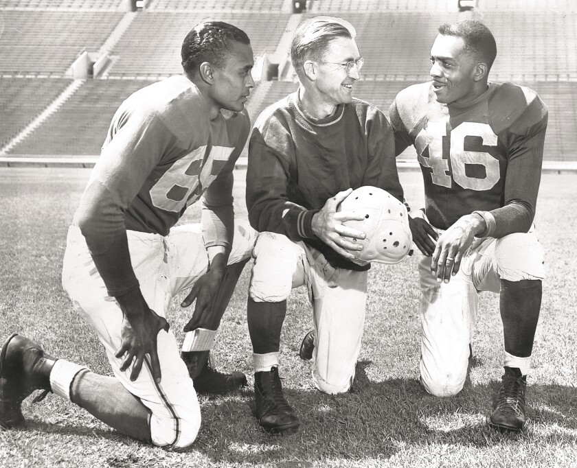 Two Black players and white coach kneel in black-and-white photo