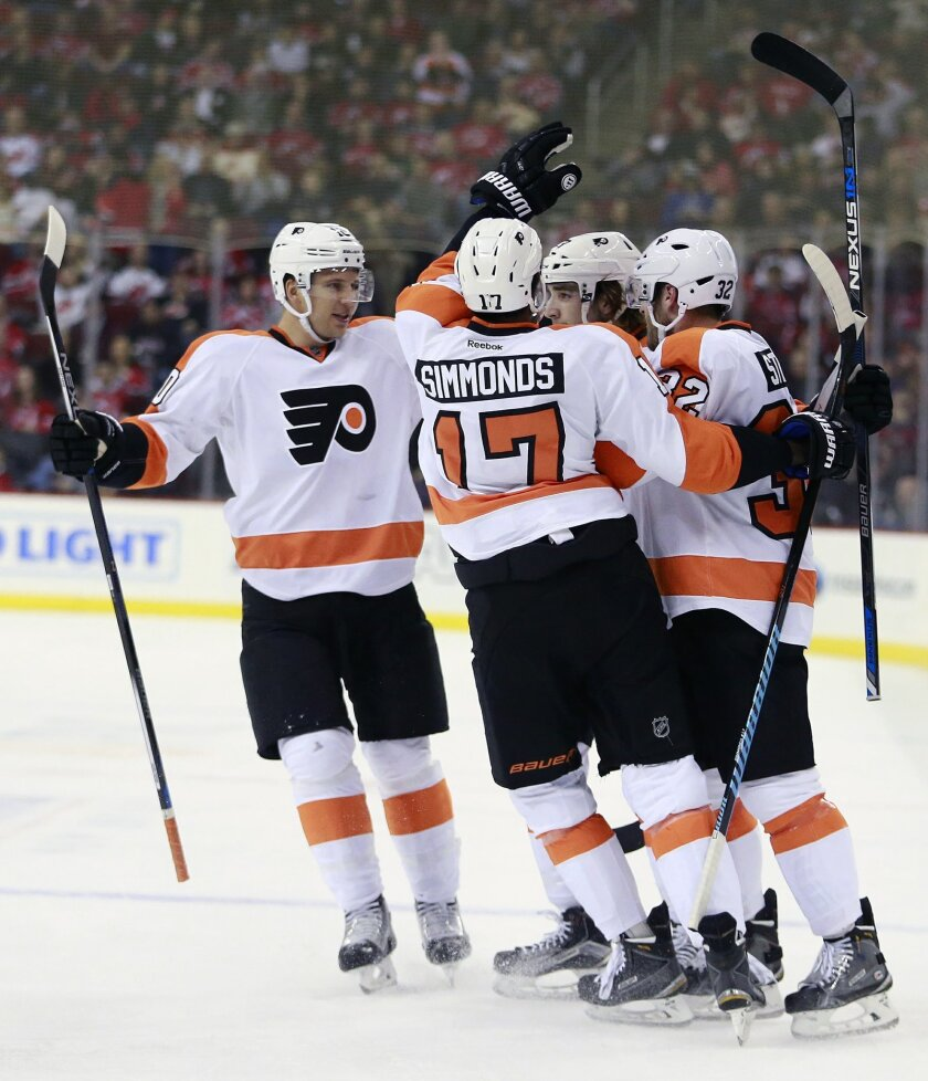 Philadelphia Flyers players celebrate a goal by defenseman Shayne Gostisbehere, center right, after scoring a goal against the New Jersey Devils during the first period of an NHL hockey game, Tuesday, Feb. 16, 2016, in Newark, N.J. (AP Photo/Julio Cortez)