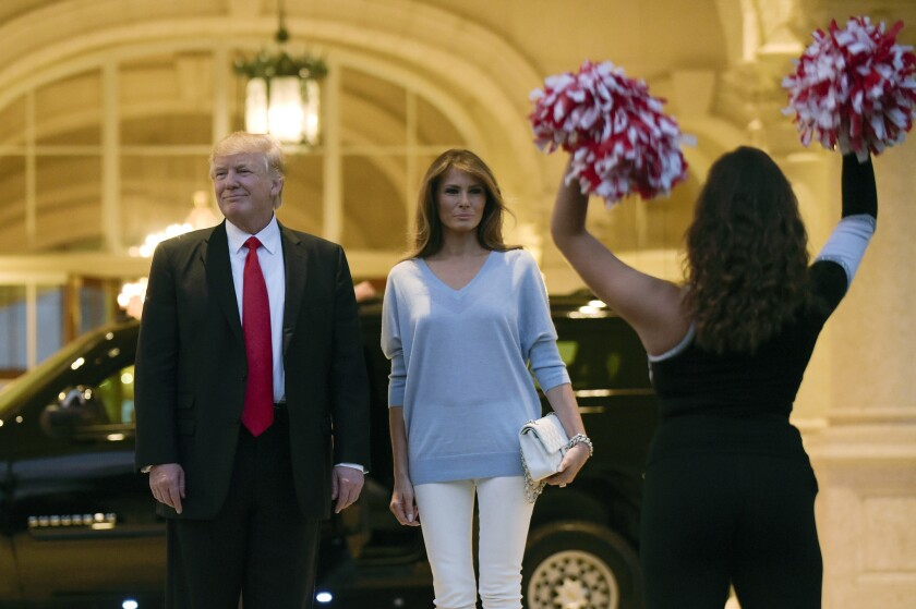 President Donald Trump and first lady Melania Trump watch the Palm Beach Central High School Band as they play for their arrival at Trump International Golf Club in West Palm Beach, Fla., Sunday, Feb. 5, 2017.