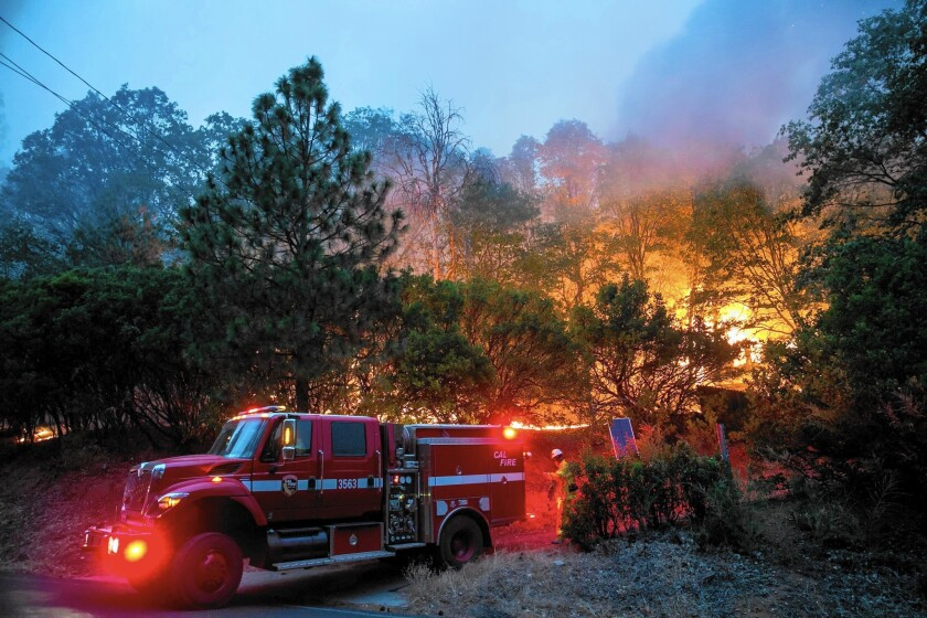 """One caller to radio station KPFZ-FM in Lakeport, Calif., said, """"You're the glue that holds the county together."""" Above, firefighters leave an area in Seigler Springs where the Valley fire destroyed a home."""