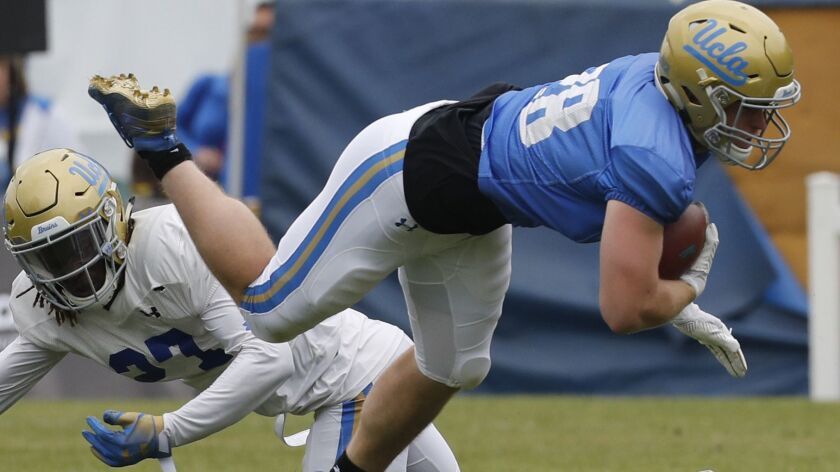 UCLA running back Cole Kinder gets tripped up by Patrick Jolly during the Bruins' spring game in April.