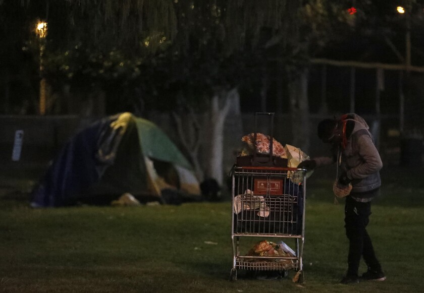 A homeless person stands with his belongings on the first night of this year's L.A. County homeless count in North Hollywood.