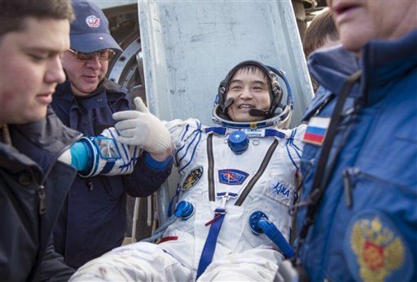 El astronauta japonés Takuya Onishi es asistido al bajarse de la cápsula Soyuz MS-01 poco después de que junto con la estadounidense Kate Rubins y el ruso Anatoly Ivanishin aterrizaran en una zona remota cerca del poblado de Zhezkazgan en Kazajistán el 30 de octubre del 2016.