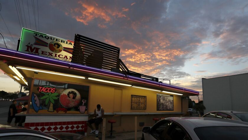 Fiery clouds drift over a taco stand in Long Beach, where monsoon-like weather will continue through Thursday before flowing out of the region.