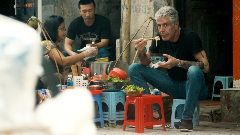 Anthony Bourdain eats with chopsticks sitting on a low stool.
