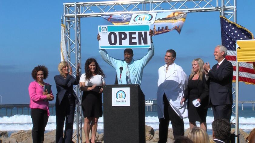 "Covered California officials, one with a large ""OPEN"" sign, announce the state insurance market opening at the beach in 2013."