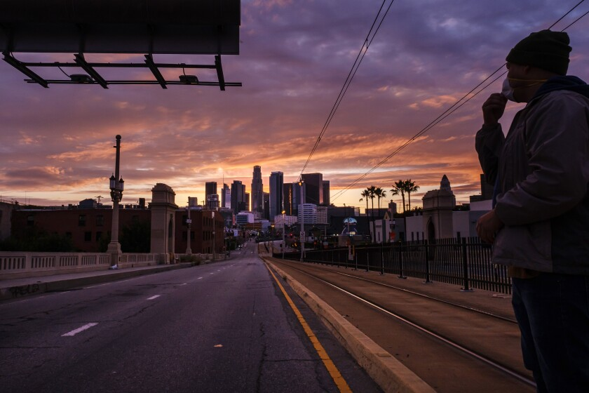 Alexander Martinez stands alone on the 1st Street Bridge as the sun sets behind a deserted downtown Los Angeles on Monday.