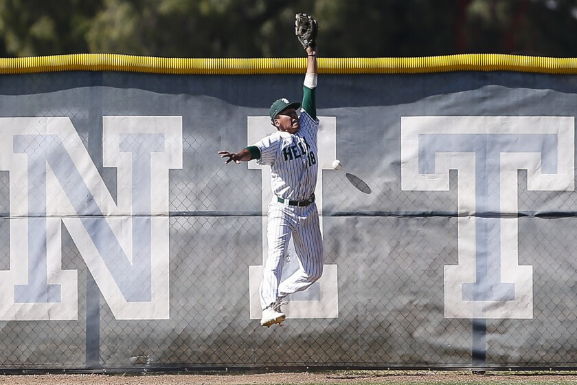 Helix left fielder Justin Cervantes can't make a catch as the ball bounces off the fence during the start of a 13 run third inning for Desert Oasis.