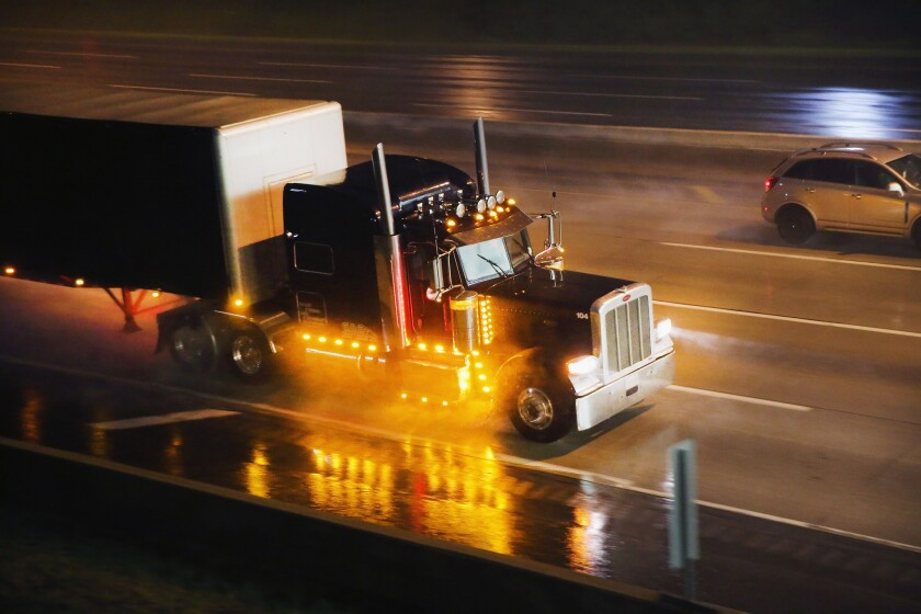 A truck driver navigates a rain-covered highway on the outskirts of Chicago.