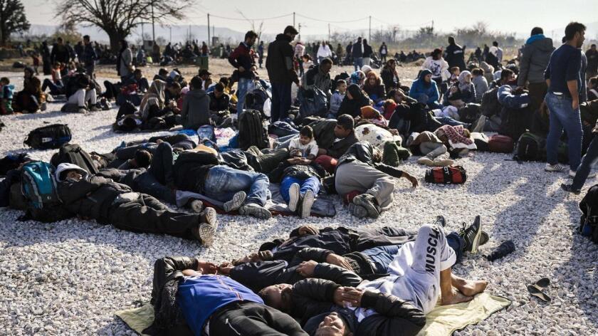 Refugiados sirios esperan ser registrados al cruzar la frontera de Grecia y Macedonia.