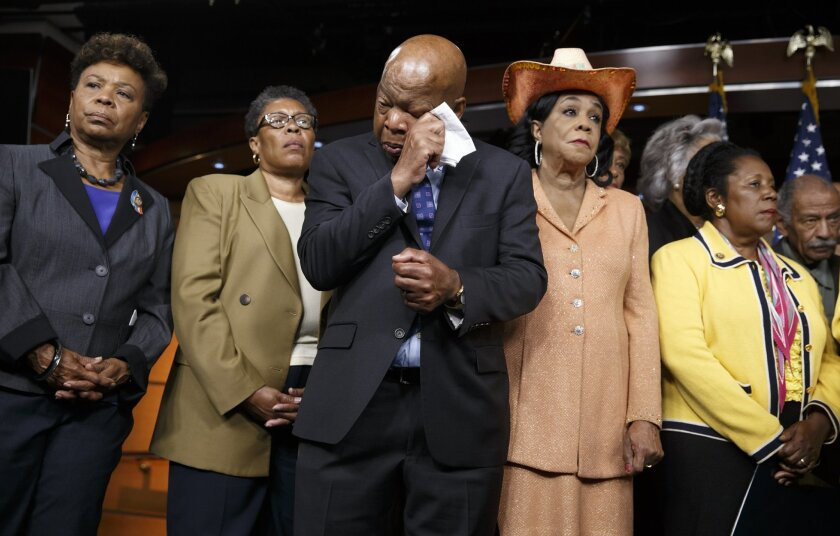 Civil right leader Rep. John Lewis, D-Ga., center, wipes his eyes as members of the Congressional Black Caucus make emotional statements condemning the slayings of police officers in Dallas last night, and the fatal police shootings of black men in Louisiana and Minnesota earlier in the week, during a news conference on Capitol Hill in Washington, Friday, July 8, 2016. From left are: Rep. Barbara Lee, D-Calif., Rep. Marcia L. Fudge, D-Ohio, Rep. John Lewis, D-Ga., Rep. Frederica Wilson, D-Fla., and Rep. Sheila Jackson Lee, D-Texas. (AP Photo/J. Scott Applewhite)