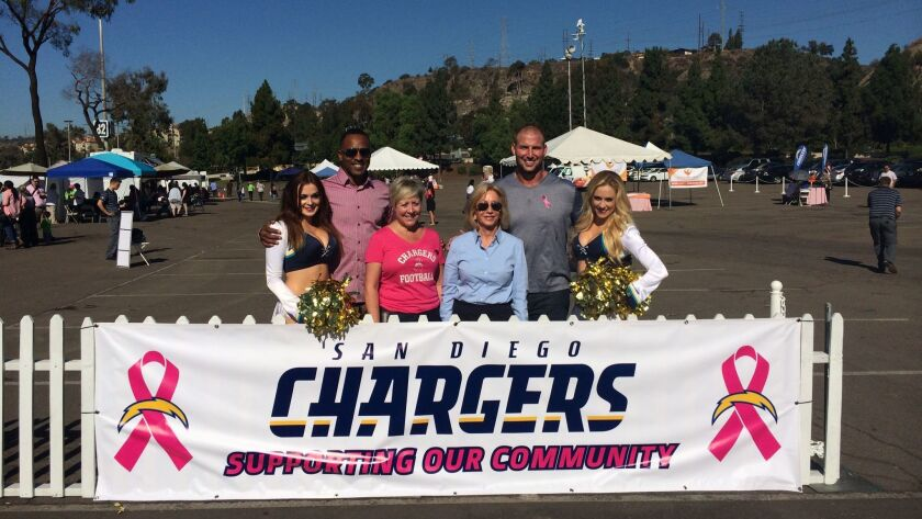 Chargers cheerleaders and former Chargers Darren Carrington (left) and Nick Hardwick with Komen San Diego CEO/President Laura Farmer Sherman and Susie Spanos, wife of Chargers owner Dean Spanos, Chargers, a breast cancer survivor.