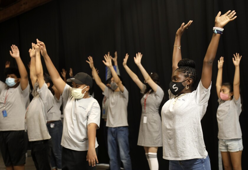 Young people, standing in rows, lift up their arms.