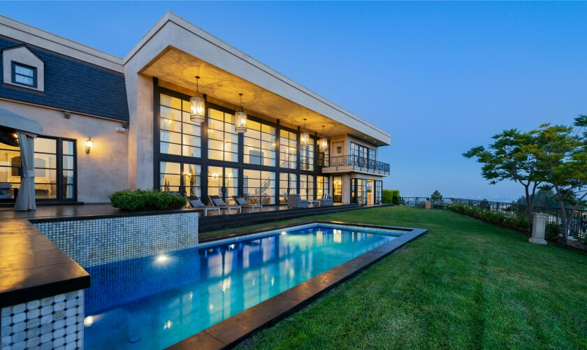 Perched above the Sunset Strip, the modern home holds a two-story great room that leads to a solar-heated saltwater pool.