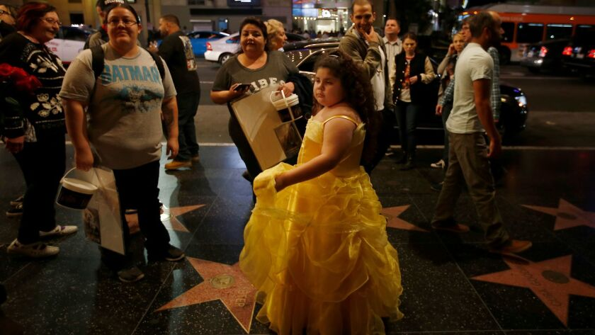 """Dressed in yellow as Belle, Samantha Ruiz, 7, of Monterey Park leaves Hollywood's El Capitan Theatre after the first L.A. public screening of """"Beauty and the Beast"""" on Thursday."""