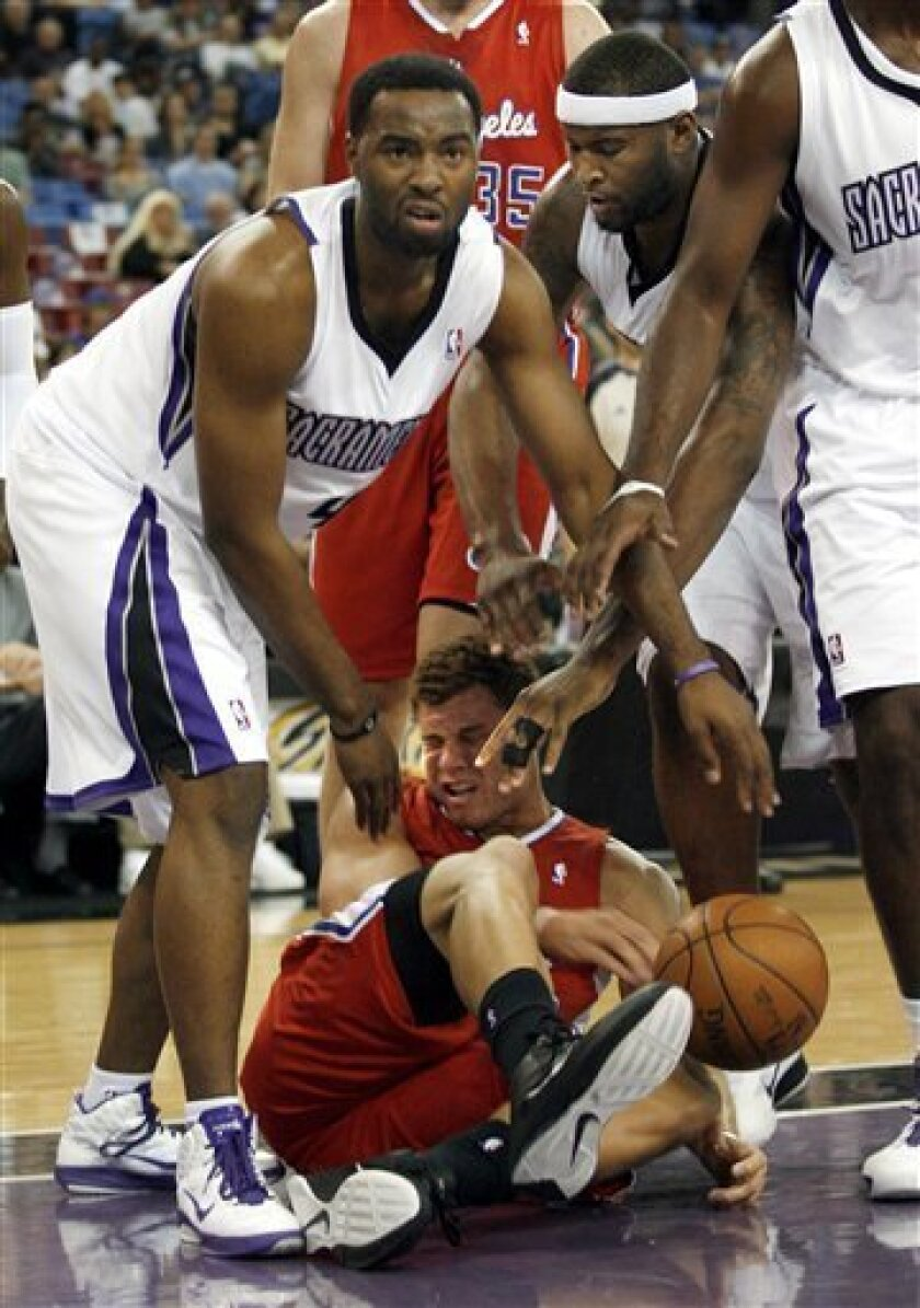 Los Angeles Clippers' Blake Griffin, bottom, takes a tumble between Sacramento Kings' Marcus Landry, left, and DeMarcus Cousins in the first half of an NBA preseason basketball game Thursday, Oct. 7, 2010, in Sacramento, Calif. (AP Photo/Dino Vournas)