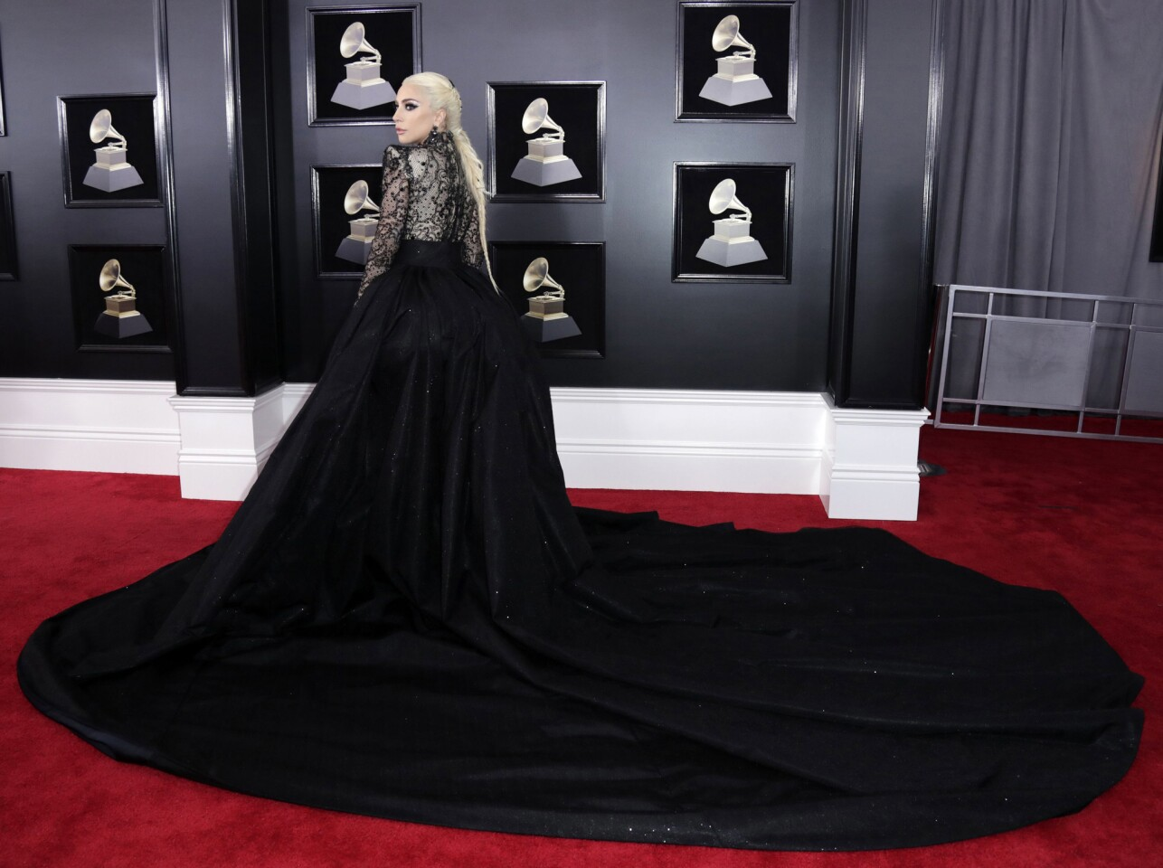 Lady Gaga cut a dramatic figure in a custom Armani Privé high-necked lace bodysuit and a billowy detachable skirt, complete with train and high-leg slit. The performer and nominee topped off the dramatic look with Lorraine Schwartz chandelier earrings embellished with more than 300 carats of black diamonds.
