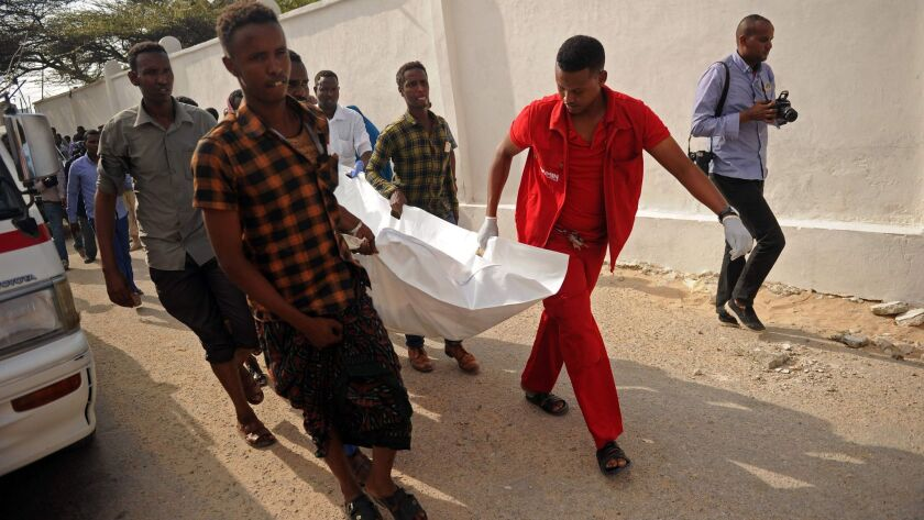 The body of a bomb blast victim is carried away in Mogadishu, Somalia.