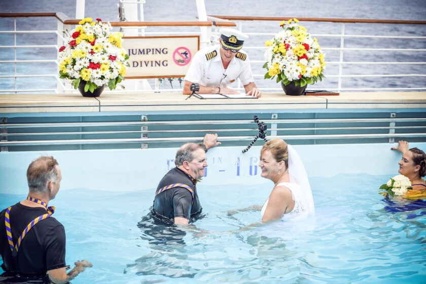 Capt. Vincenzo Lubrano presides over the wedding of Tami Van Dusen and Tim Ashley, who is quadriplegic. The Crown Princess granted their special request of removing some water from their pool to allow Tim Ashley to stand during the ceremony.