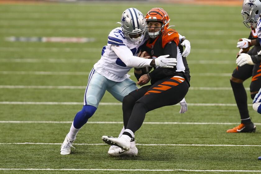 Dallas Cowboys defensive back Deante Burton (33) sacks Cincinnati Bengals quarterback Brandon Allen (8) in the second half of an NFL football game in Cincinnati, Sunday, Dec. 13, 2020. (AP Photo/Aaron Doster)