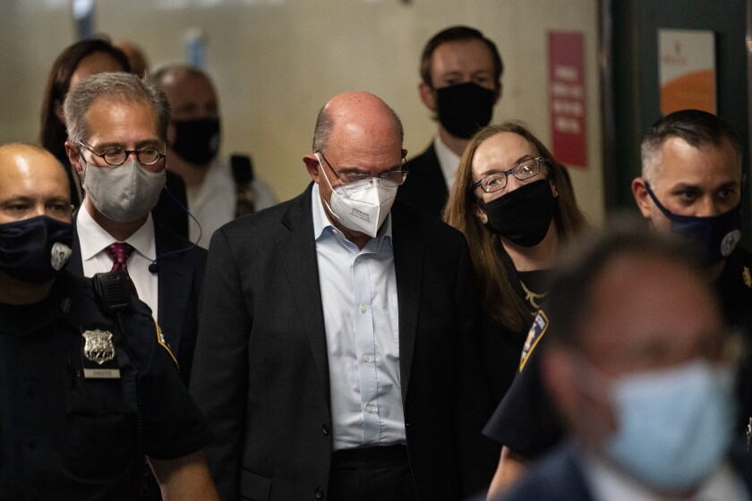 Allen Weisselberg, center, departs Manhattan criminal court, Thursday, July 1, 2021, in New York. Weisselberg was arraigned a day after a grand jury returned an indictment charging him and Trump's company with tax crimes. Trump himself was not charged. (AP Photo/John Minchillo)