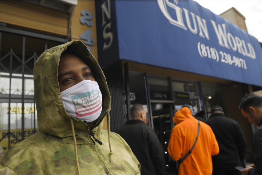 A gun store customer that gave his name only at John waits in line, Sunday, March 15, 2020, in Burbank, Calif. As consumers are buying all kinds of goods in large quantities amid coronavirus concerns, putting pressure on inventories, John stated that he was there to buy ammunition because most other stores were out and he wanted to stock up. (AP Photo/Mark J. Terrill)