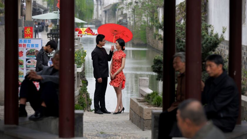 Residents take rest at a pavilion as a bride and groom, dressed a traditional costume, pose for wedd