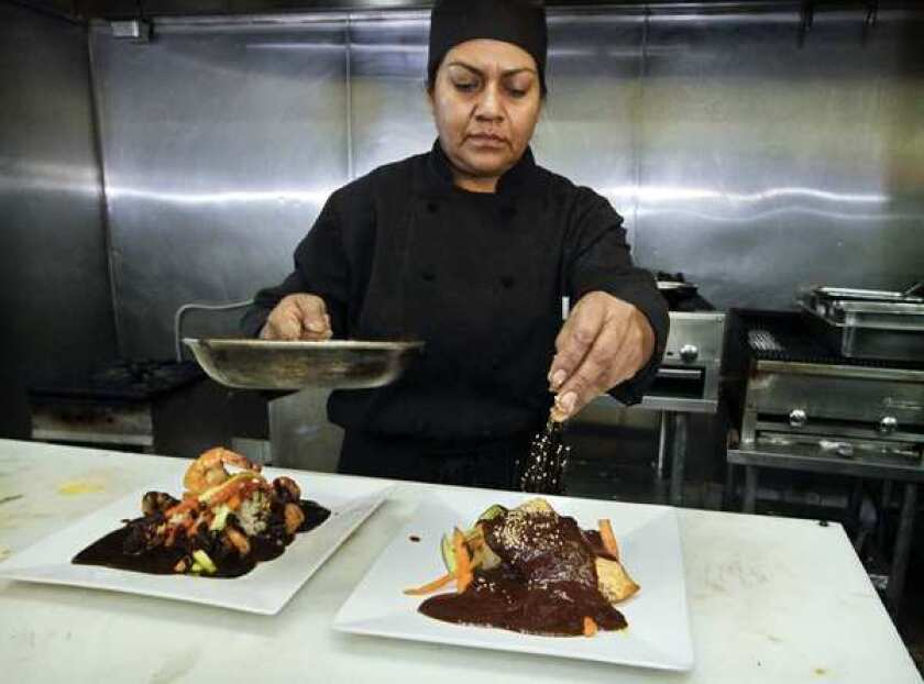 Chef Rocio Camacho, who also has a restaurant in Bell, garnishes a plate of mole poblano salmon with sesame seeds at Rocio's Mole de los Dioses restaurant.