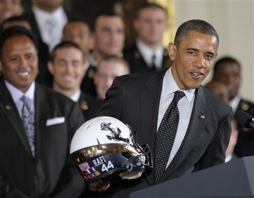 President Barack Obama holds a Navy football team helmet and explains why he won't put it on after presenting the Commander-in-Chief Trophy to the United States Naval Academy football team, Friday, April 12, 2013, in the East Room of the White House in Washington. Head coach Ken Niumatalolo watches