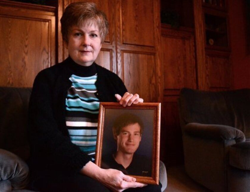 In this Feb. 16, 2013 photo, Karen Williams poses with a photo of her deceased son, Loren, in Beaverton, Ore.. Williams, who battled Facebook over the right to view Loren's Facebook page, has been urging lawmakers for years to do something to prevent others from losing photos, messages and other me