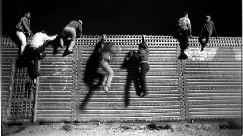 Having caught the U.S. Border Patrol off guard, a group of young men jump down the north side of the