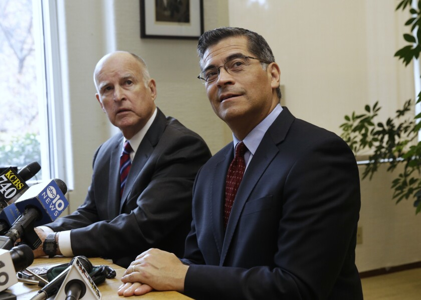 Gov. Jerry Brown, left, and Rep. Xavier Becerra (D-Los Angeles), Brown's nominee for state attorney general, listen to a reporter's questions during a news conference last month.