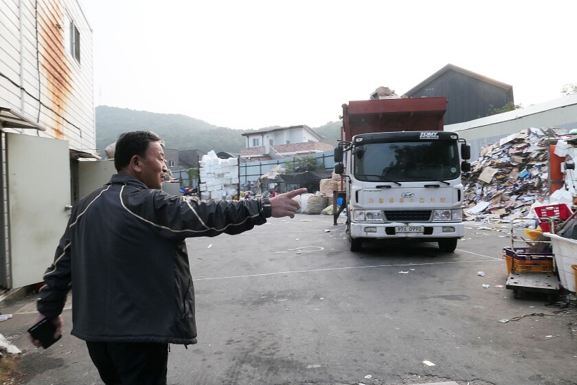 Lee Yong-gi, a operator of a recycling collection company, walks through his recycling center in Goyang, South Korea.