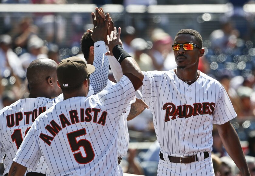 San Diego Padres' Melvin Upton Jr., right, is congratulated at the dugout after scoring against the Atlanta Braves in the seventh inning of a baseball game Wednesday, Aug. 19, 2015, in San Diego. (AP Photo/Lenny Ignelzi)
