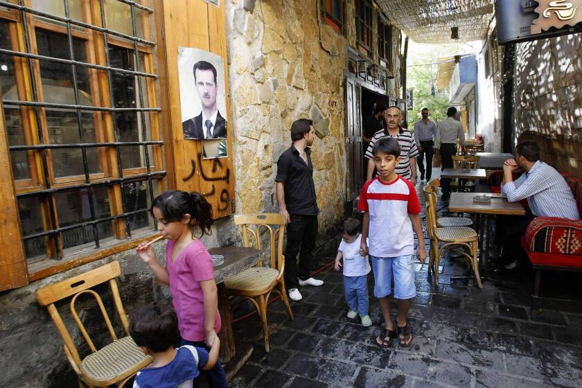 People make their way at a restaurant bearing a poster of President Bashar Assad in Damascus, Syria's capital. For residents, the routines of life continue, but the war is never far away.