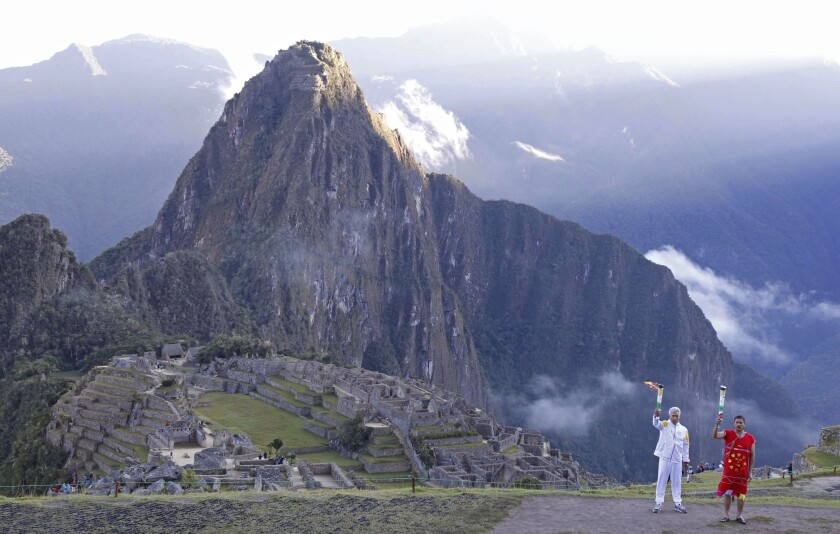 In this handout photo provided by the Lima2019 Pan American Sports Organization, Peru's Culture Minister Fernando Astete Victoria, in white, takes part in a ceremony marking the arrival of the Pan Am flame to the Machu Picchu archeological site in Cuzco, Peru, Thursday, July 4, 2019. The Pan American Games begin July 26 and run through Aug. 11, 2019, in Lima. (German Falcon/Lima2019 Pan American Sports Organization via AP)