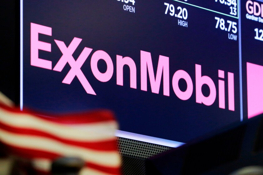 FILE - In this April 23, 2018, file photo, the logo for ExxonMobil appears above a trading post on the floor of the New York Stock Exchange. Exxon Mobil plans to reduce the number of oil rigs operating in an oil-rich region in the Southwest and may cut planned capital expenditures as crude prices sink. The price of a barrel of oil has fallen more than 20% since the start of the year, and 8% in the last month, with energy demand expected to shrink as the spreading coronavirus drags on the global economy. (AP Photo/Richard Drew, File)
